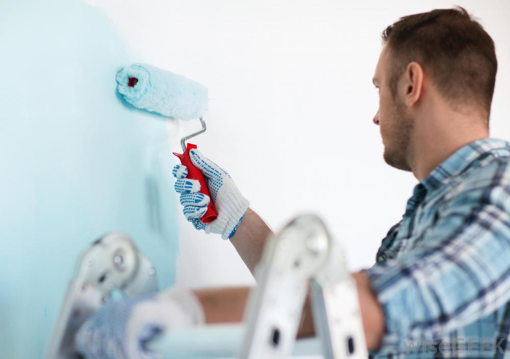 man-with-roller-painting-wall-blue